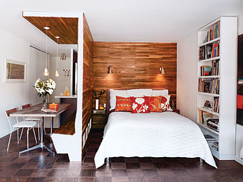 A walnut divider separates the bedroom from the dining room.