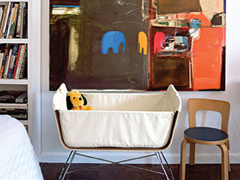 Baby bassinet under a big painting