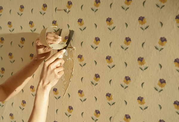 Woman peeling wallpaper