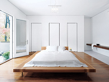 A walnut bed by Cappellini floats in the master bedroom.