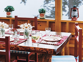 The family uses the cabin's second-floor porch for dining and playing board games.
