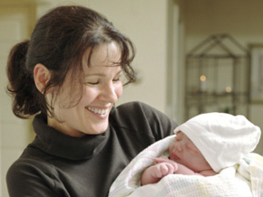 A doula holds a baby