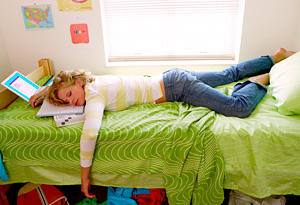 College student asleep on dorm room bed