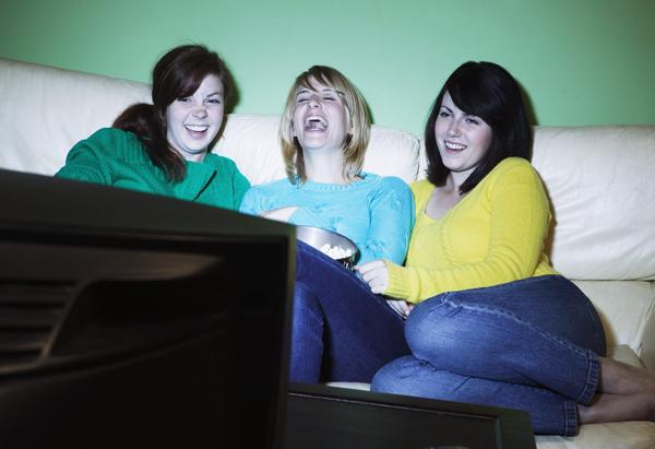 Three women watching television