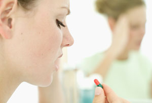 Woman contemplating taking pills