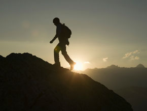 Climber reaching mountain summit
