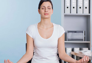 Woman meditating on desk chair