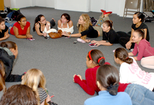 Elizabeth Berkley and young women sitting in a circle