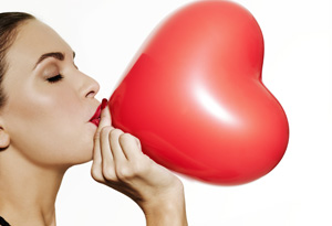 Woman blowing up heart balloon