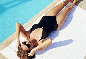 Woman tanning poolside