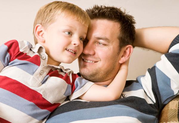 Dad hugging little son