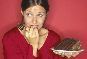 Conflicted woman holding cake