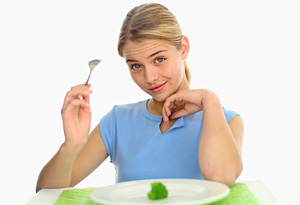 Teen eating broccoli