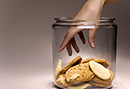 Woman with hand in cookie jar.