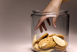 Woman reaching into cookie jar