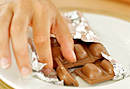 Woman reaching for chocolate.