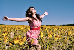 Girl running through sunflowers