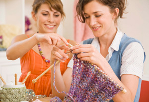 Woman helping another knit