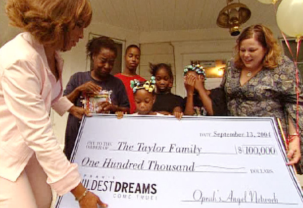 Connie Taylor with check from Oprah's Angel Network for new home