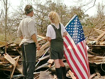 Jennifer sticks an American flag on what used to be her home.