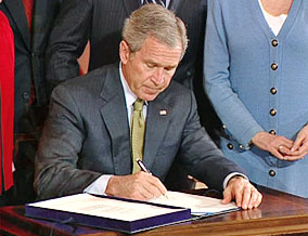 President Bush signs into law the Trafficking Victims Protection Reauthorization Act