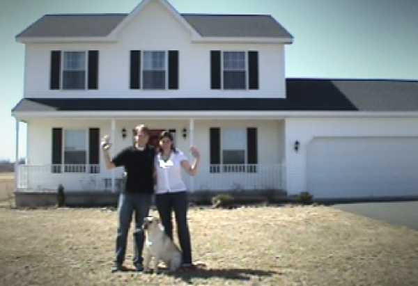 Carmela and her husband in front of their new house