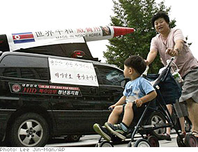 South Koreans pass a protest of North Korean missile launchers.