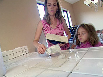Zigi regrouts her countertop as her daughter looks on.