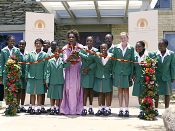 Oprah and the new students cut the ribbon on Oprah's leadership academy.