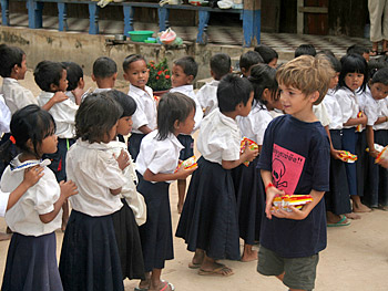 Kieran passes out food in Cambodia.