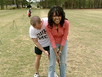 Dave helps Katina with her swing at the driving range.
