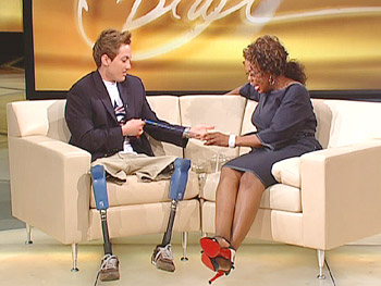 Rudy shows Oprah his Paralympic gold medal.