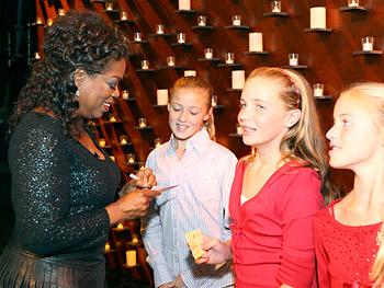 Oprah signs an autograph.