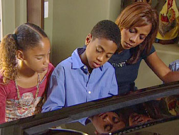 R.J. plays the piano for his mother and sister.