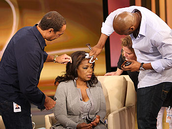 The finishing touches are made to Oprah's hair and makeup.