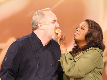 Oprah gives Chef Art Smith a bite of his famous biscuits.