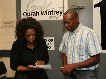 Oprah signs an autograph.
