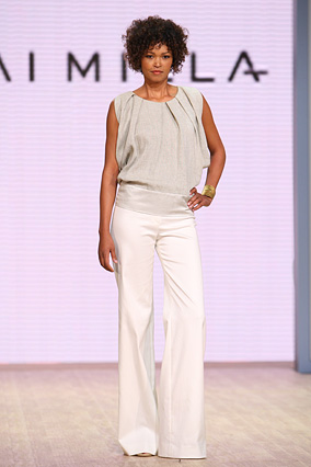 A light gray rough linen pleated top and white stretch boot-cut pants.