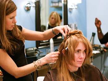 A hairstylist works on attaching some hair extensions.