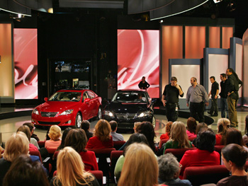 Cars are arranged before Oprah parallel parks onstage.