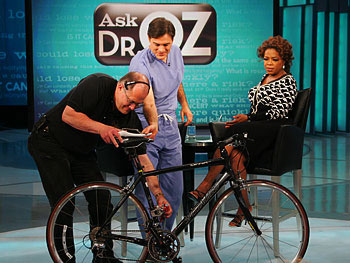 A Harpo employee helps set up a bicycle onstage.