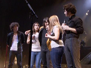 The Jonas Brothers surprise Alessandra and Kim onstage.