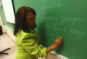 Denni Foster writing on a chalkboard