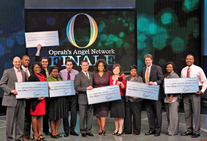 Oprah hands out Angel Network checks.