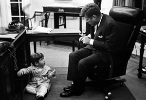 John F. Kennedy Jr. plays under his father's desk.