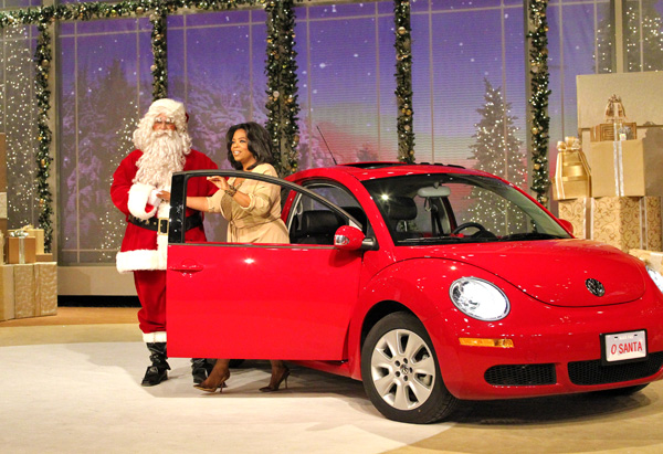 Oprah getting out of a red Volkswagen Beetle