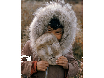 A Nunamiut boy holds a mask made of caribou hide