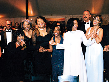 Maya Angelou (center) is serenaded by (from far left) Patti Labelle, Nancy Wilson, Rosa Johnson, Oprah, Stedman, and Gayle